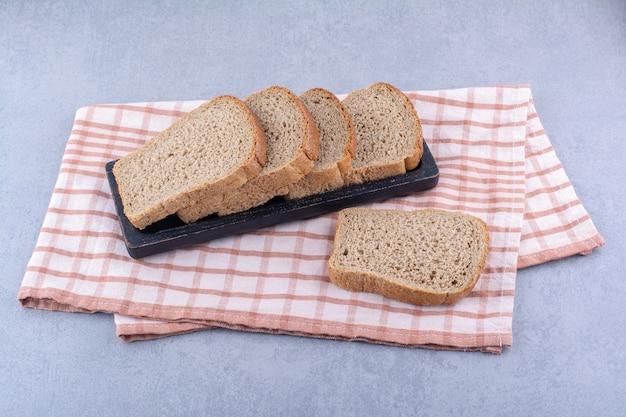 Bandeja preta com fatias de pão integral em uma toalha dobrada sobre superfície de mármore