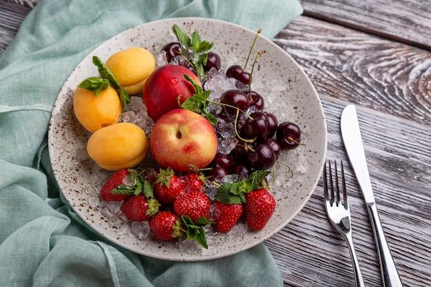 Bandeja saudável da fruta, morangos, maçãs, pêssegos, abricós em uma tabela de madeira cinzenta escura, vista superior, close-up, foco seletivo.