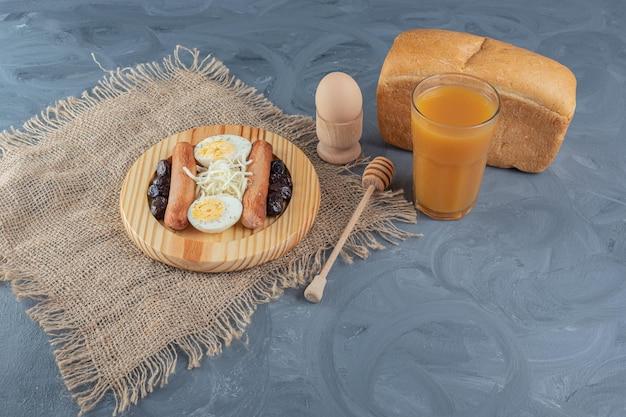 Bandeja variada de café da manhã ao lado de um pão, suco de pêssego, ovo cozido e uma colher de mel na mesa de mármore.