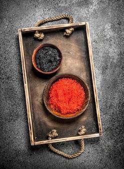 Bandeja velha com caviar preto e vermelho. sobre fundo rústico.