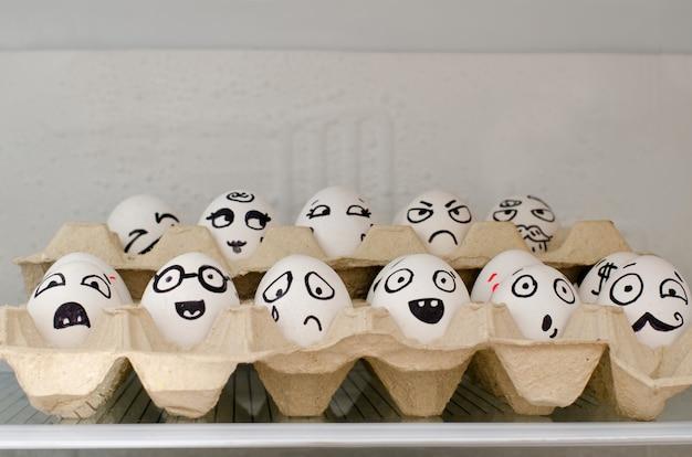 Bandejas com ovos na geladeira, emoções pintadas close-up