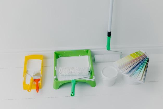 Bandejas com rolos de pintura, balde com cores e amostras de cores. conceito de renovação de casa.