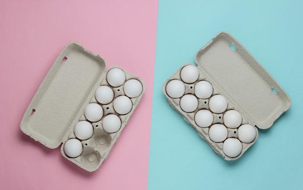 Bandejas de papelão com ovos em fundo rosa azul pastel. conceito de culinária minimalista