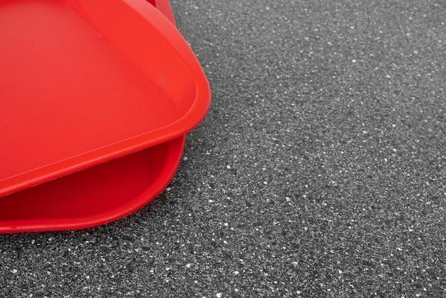 Bandejas de plástico vermelhas vazias em uma mesa de cozinha preta. foco seletivo