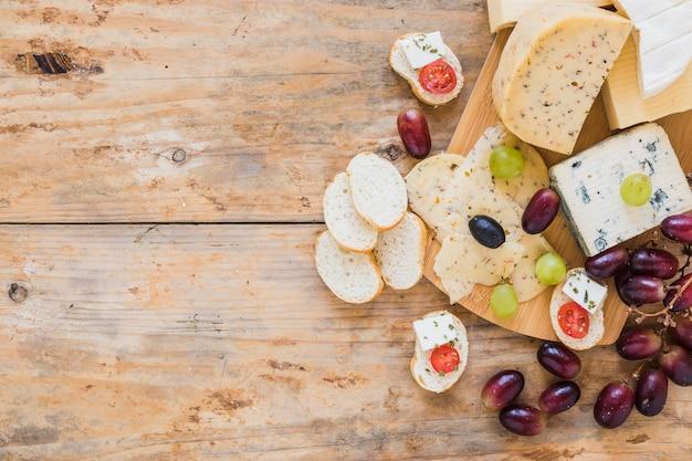 Bandejas de queijo com uvas e pão na mesa de madeira