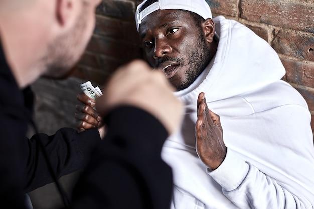 Bandido rouba homem africano. cara caucasiano está ameaçando homem negro assustado, homem afro-americano com medo está chocado sentado no chão, dando dinheiro. na rua. agressão, crime, conceito de violência