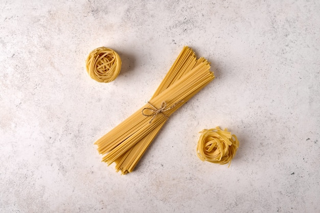 Bando cru de espaguete fettuccine e tagliatelle cru no espaço de cópia de plano de fundo texturizado cinza