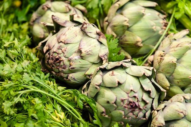 Bando de alcachofras recém-colhidas em um jardim, legumes para uma dieta saudável, mercado de alimentos