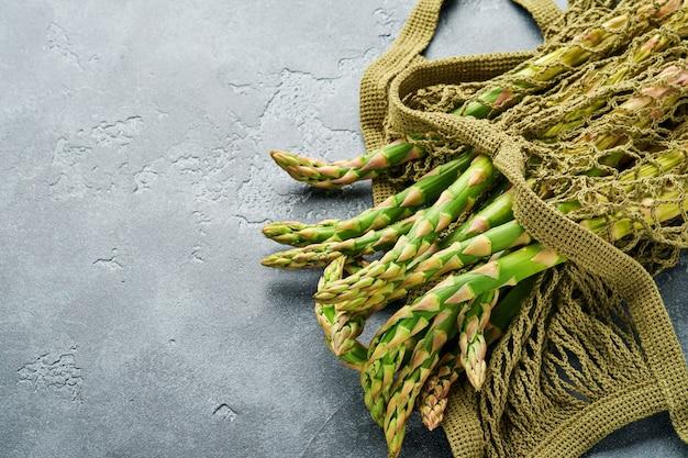 Bando de aspargos verdes frescos prontos para cozinhar no fundo da mesa de pedra de ardósia cinza