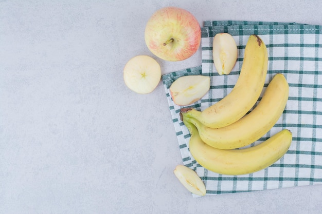 Bando de banana de fruta madura com maçã fatiada na toalha de mesa. foto de alta qualidade