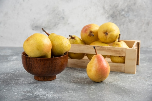 Bando de bio peras frescas em caixa de madeira e tigela.