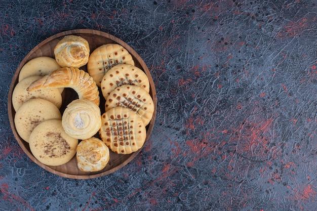 Bando de biscoitos em uma pequena bandeja na mesa abstrata.