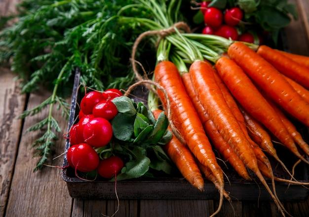 Bando de cenouras frescas com folhas verdes e um monte de rabanetes
