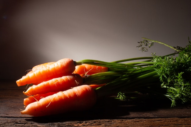 Bando de cenouras frescas em fundo de madeira rústica