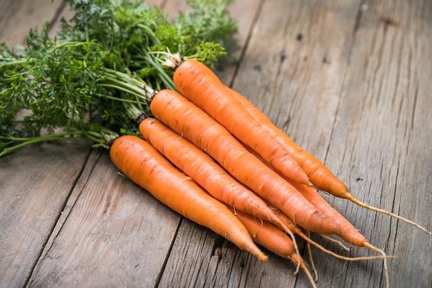 Bando de cenouras frescas em fundo rústico. alimentos vegetais vegan saudáveis.
