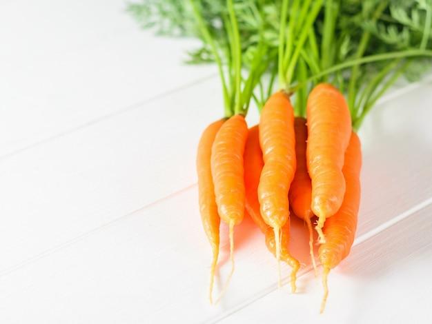 Bando de cenouras frescas em uma mesa de madeira branca.