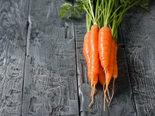 Bando de cenouras frescas em uma mesa de madeira escura