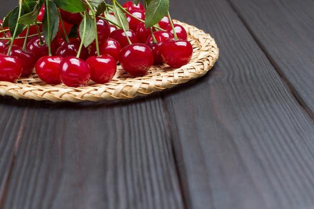 Bando de cerejas na mesa. fundo de madeira. vista do topo. copie o espaço