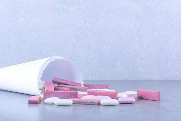 Bando de chicletes caindo do papel de embrulho na superfície de mármore Foto gratuita