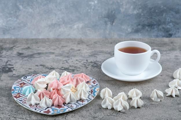Bando de doces de merengue coloridos em um tripé em forma de coração e uma xícara de chá.