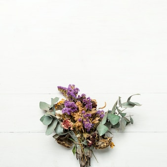 Bando de ervas secas e flores na superfície branca