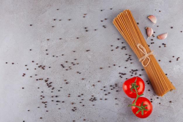 Bando de espaguete de grãos inteiros amarrado com corda e tomates vermelhos frescos.