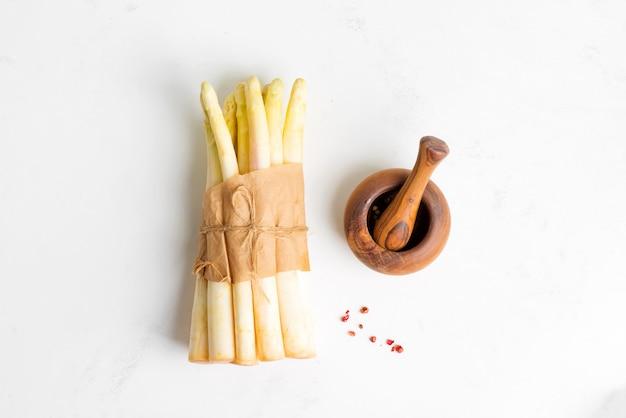 Bando de espargos brancos orgânicos crus recém-colhidos e argamassa de madeira com papel