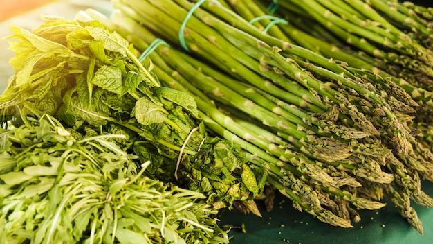 Bando de espargos com rúcula e hortelã no mercado