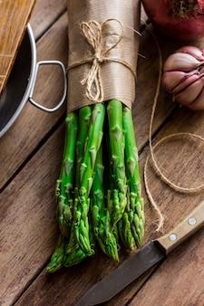 Bando de espargos frescos amarrados com barbante, utensílios de cozinha de faca de alho na mesa de madeira
