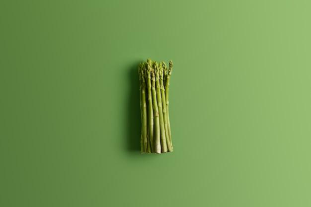 Bando de espargos frescos em fundo verde vívido. ingrediente para preparar deliciosa salada vegetariana. conceito de comida. legumes frescos da primavera. brotos comestíveis de aspargos ricos em vitaminas, ácido fólico