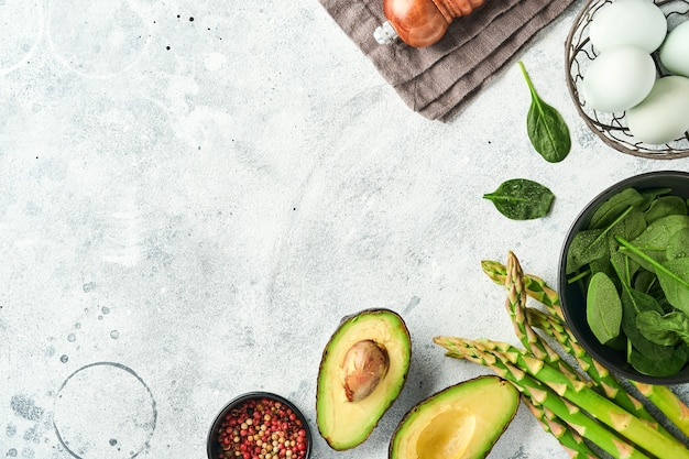 Bando de espargos verdes frescos e orgânicos, espinafre, abacate, ovos de galinha e tempero de pimenta