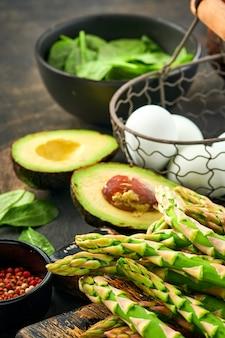Bando de espinafre de aspargos verdes frescos, abacate, ovos de galinha e tempero de pimenta na superfície de madeira velha preta, vista superior. cozinhar alimentos com espaço de cópia.