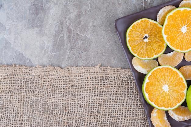 Bando de fatias de tangerina e segmentos na placa preta.