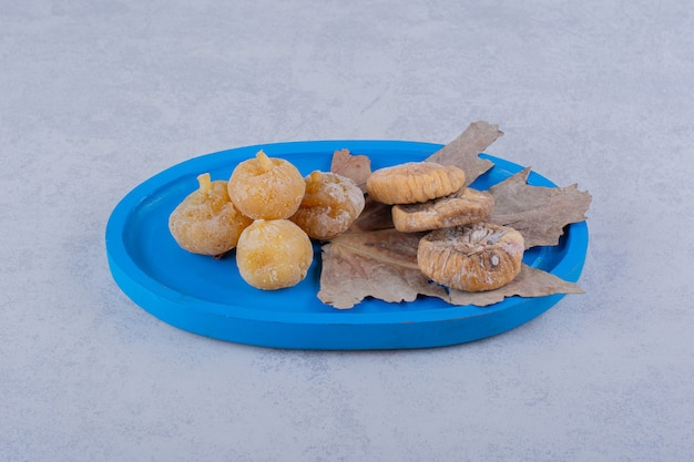Bando de figos secos doces colocados no prato azul.