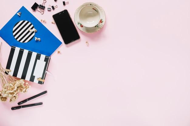 Bando de flores brancas com artigos de papelaria; telefone móvel e copo vazio no pano de fundo rosa