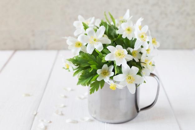Bando de flores de primavera branca em caneca de ferro