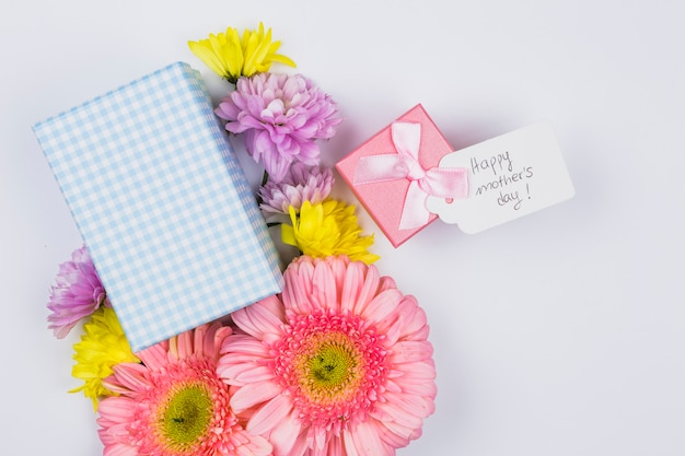 Bando de flores frescas perto de tag com palavras e caixas de presentes