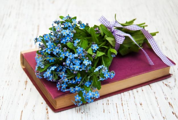 Bando de flores miosótis e livro antigo