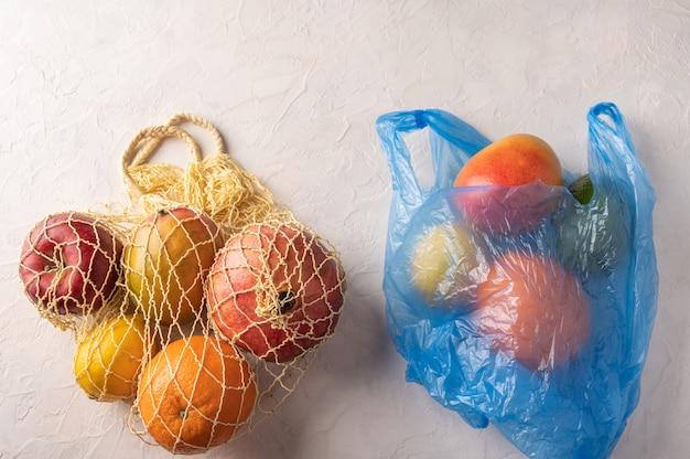 Bando de frutas orgânicas misturadas, vegetais e verdes em um saco de barbante e plástico sobre fundo claro.