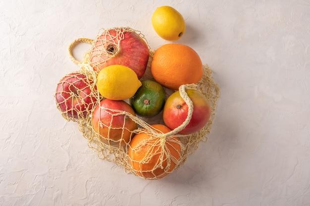 Bando de frutas, vegetais e verdes orgânicos misturados em um saco de barbante sobre fundo claro.
