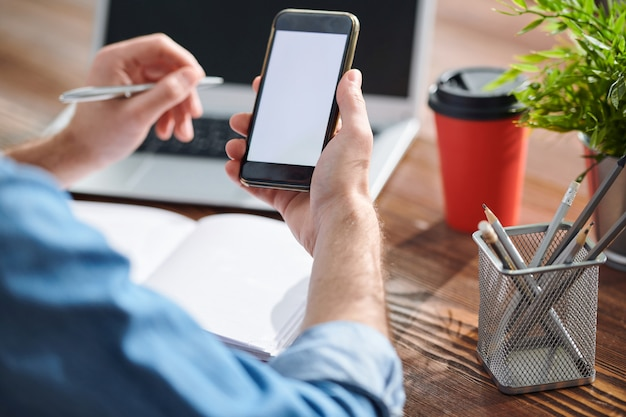 Bando de lápis em um recipiente plástico e as mãos do empresário segurando o smartphone enquanto o usa