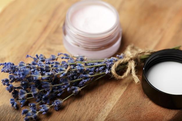 Bando de lavanda e cosmético pote em uma mesa de madeira