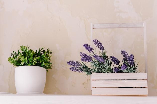 Bando de lavanda em uma caixa de madeira e vegetação em um vaso sobre uma mesa branca em uma prateleira vintage sobre parede pastel. decoração interior provençal chique para o estilo de casa de fazenda. decoração de casa provençal.