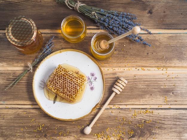 Bando de lavanda; pote de mel; e pedaço de favo de mel na placa sobre a mesa