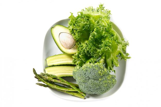 Bando de legumes isolados. pilha de legumes frescos em chapa branca. dieta vegetal verde.