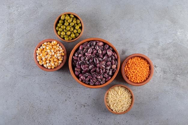Bando de lentilhas cruas, feijão e arroz em fundo de pedra.