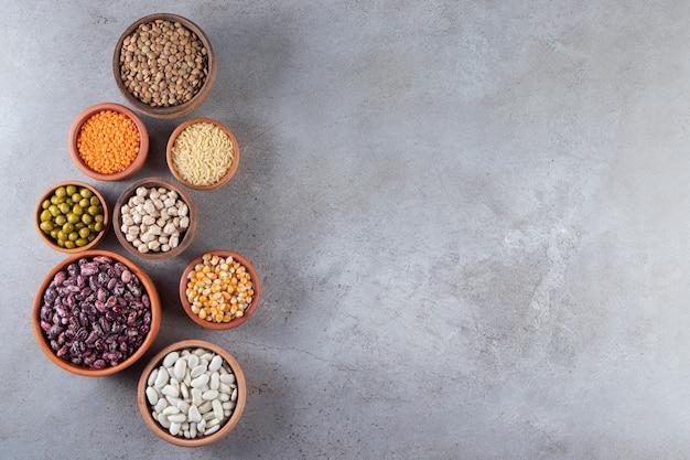 Bando de lentilhas cruas, feijão e arroz no fundo de pedra.
