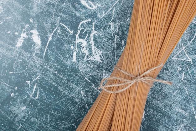 Bando de macarrão de espaguete de grãos inteiros amarrado com corda no espaço de mármore.