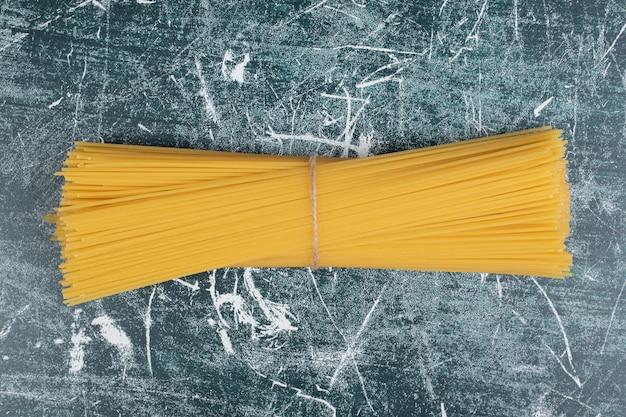 Bando de macarrão de espaguete de grãos inteiros amarrado com corda no fundo de mármore. foto de alta qualidade