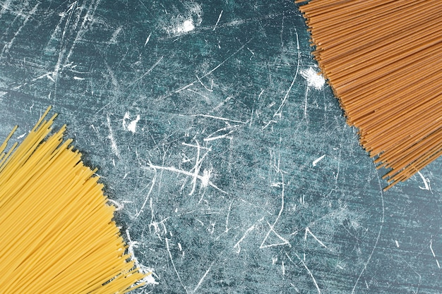 Bando de macarrão despreparado de espaguete de grão integral em fundo de mármore